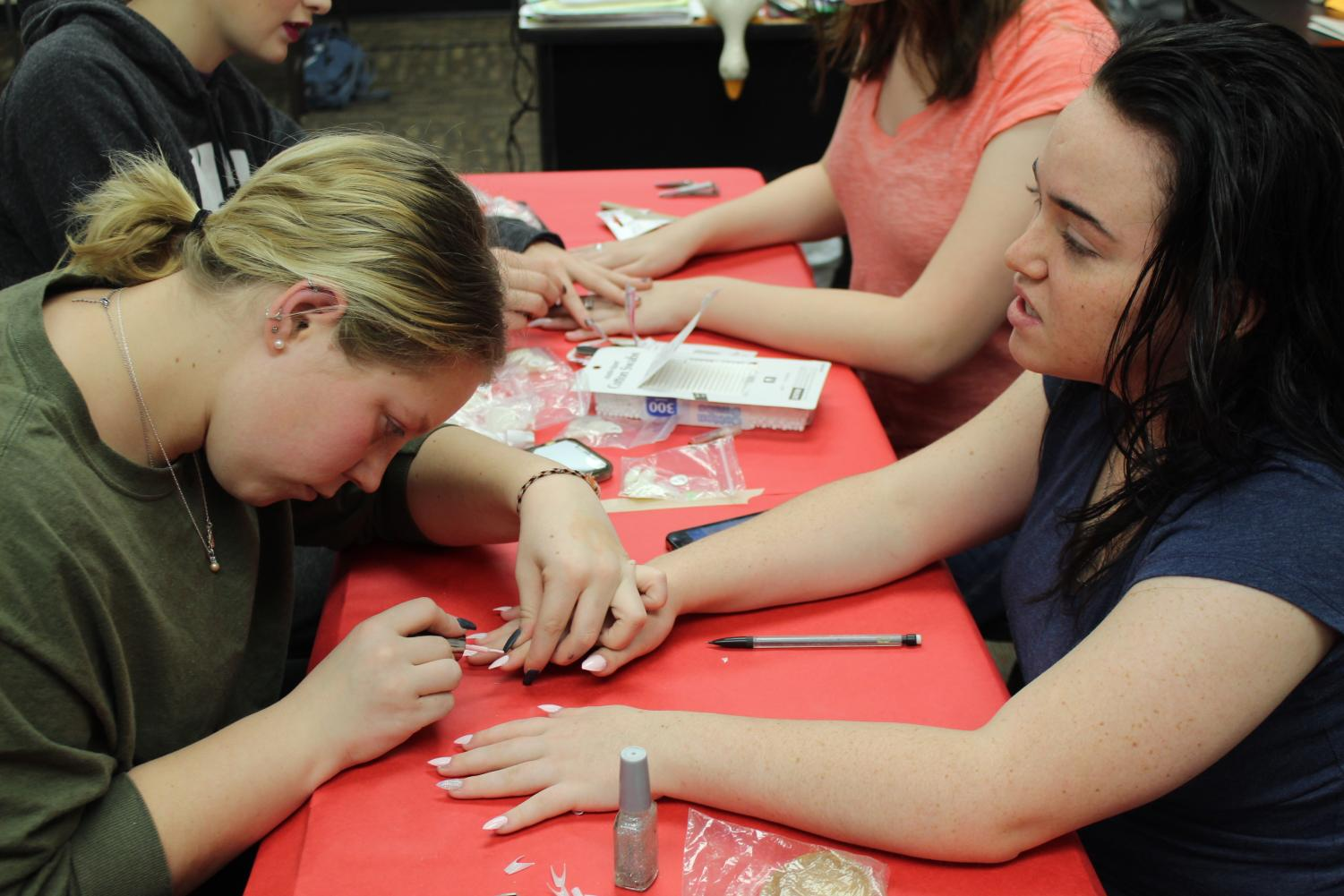 Ally Davis (11) paints Alexis Wilson's (11) nails. Davis volunteered to help with Operation Cinderella, which started with hair and makeup at 9 a.m. Saturday Dec. 15.