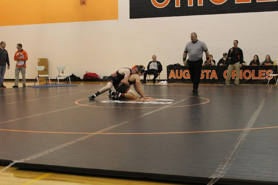Dominick Ketchum (12) and Chad Mercier (12) wrestle each other during their scrimmage.  They demonstrated the referees position, Ketchum is on bottom and Mercier is covering on top.