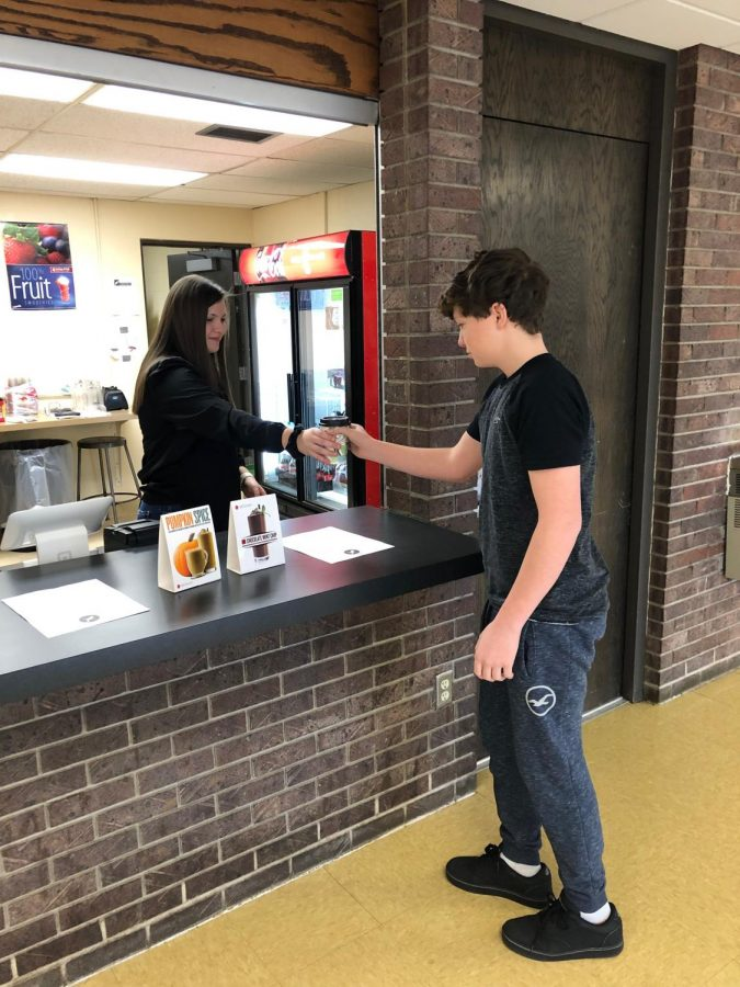 Cheyenne Pohlman (11) hands Everett Latimer (10) his beverage from the coffee shop. The Early Bird Cafe had a wide selection of blenders, smoothies and frappe.