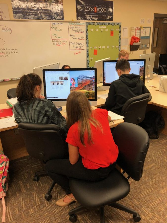 "Members of the Oriole newspaper staff, Aubrey Stueven (12) and Gracie Johnston (12) upload pictures to Johnston's story, ""Students enjoy classes with favorite teachers,"" while Jaden Laing (11) works on his story, ""Student teacher joins science department"". Half the staff works on stories while the other half creates Tweets, posts Spotlights, and photo galleries."
