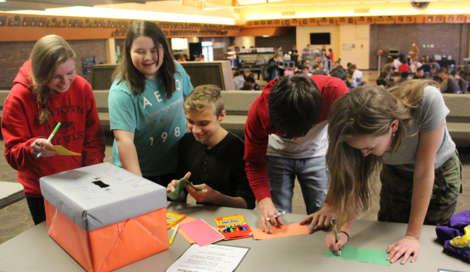 Sophomore Grace Stueven, senior Lilly White, sophomore Brendon Wedel, and sophomore Ellie Craft write kind anonymous letters to students during 2019's Kindness Week. Counselors this year decided not to do The Great Kindness Challenge because of scheduling.
