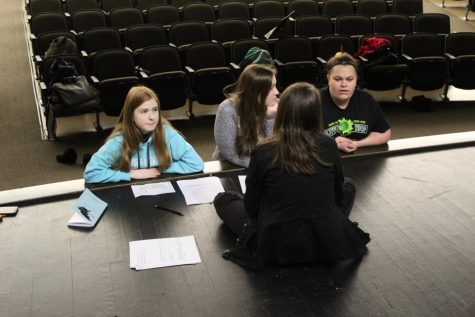 Carly Condella (11) practices lines with Amber Braddy (12), Ariana Ramseyer (9) and Katelyn Moore (12) during auditions for the play in the auditorium. Auditions were held Jan. 31 after school.