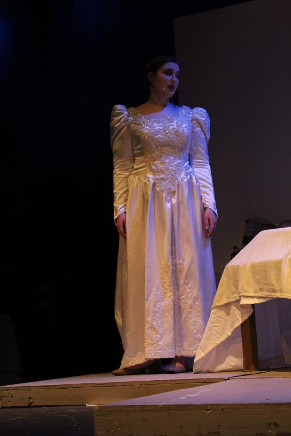 The ghost Eleanor, played by Amber Braddy (12) comforts Edgar Allen Poe on the hospital bed.