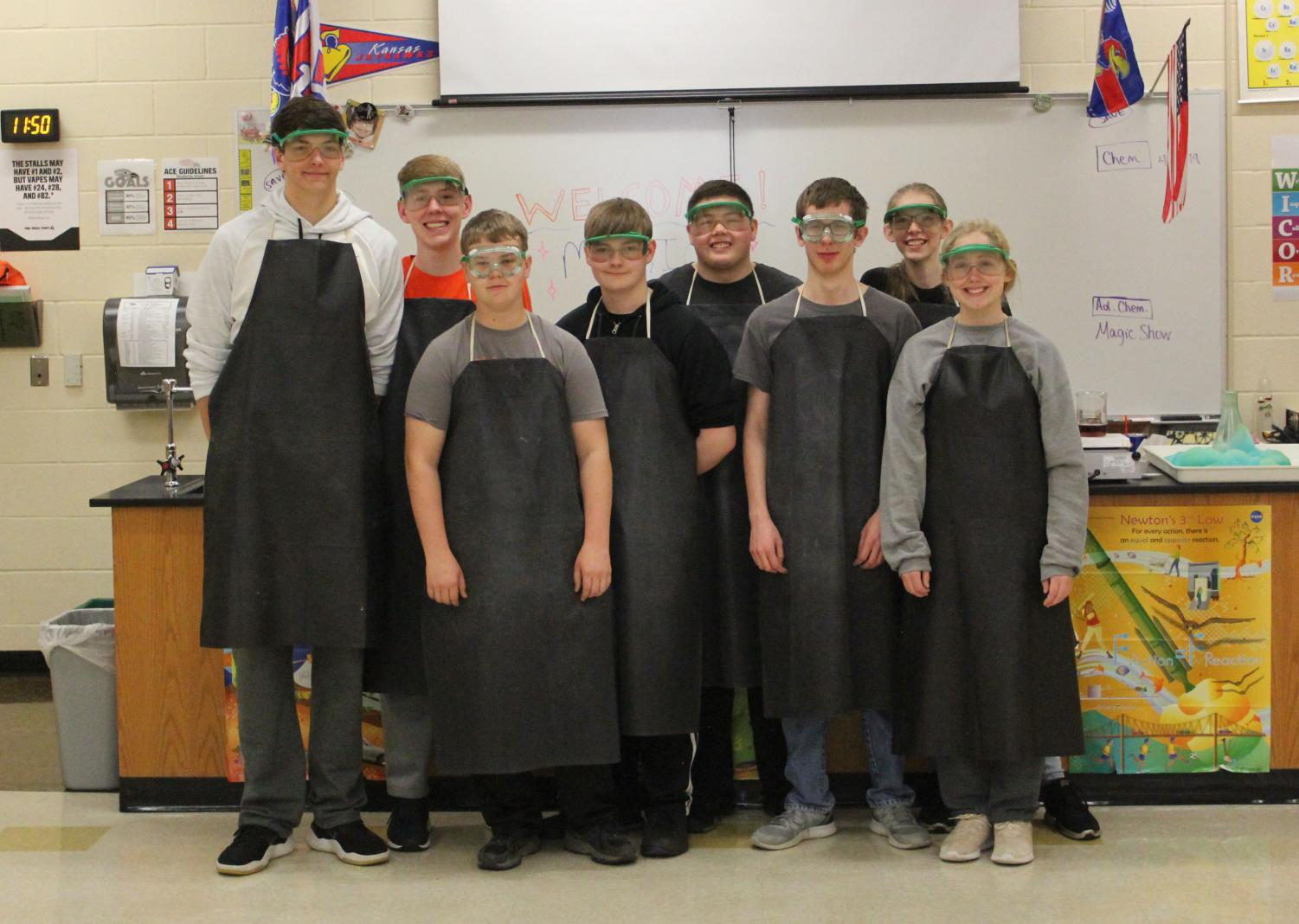 Advanced+chemistry+students+stand+in+front+of+science+teacher+Ericka+Richardson%E2%80%99s+lab+table+after+performing+their+experiments+for+elementary+students.+The+magic+show+took+place+April+4+from+11+a.m+to+noon+in+Richardson%E2%80%99s+classroom.+
