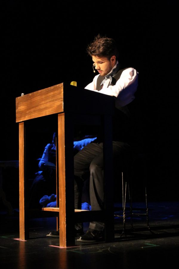 Edgar Allen Poe, played by Noah Rye (10) writes his stories on his podium.