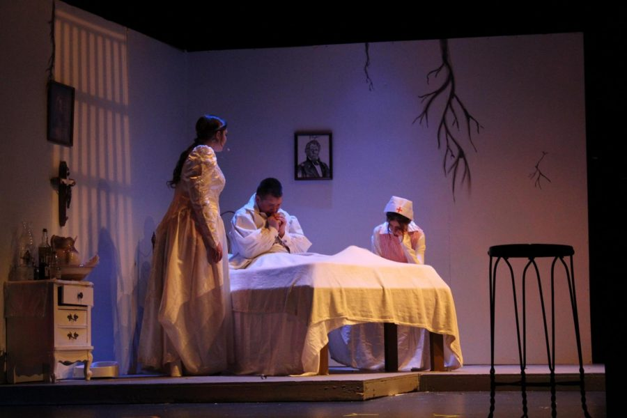 Eleanor, played by Amber Braddy (12) attempts to comfort Edgar Allen Poe, played by Gabriel Wilson (9) as the nurse, played by Juliene Fuson (9) is fast asleep.