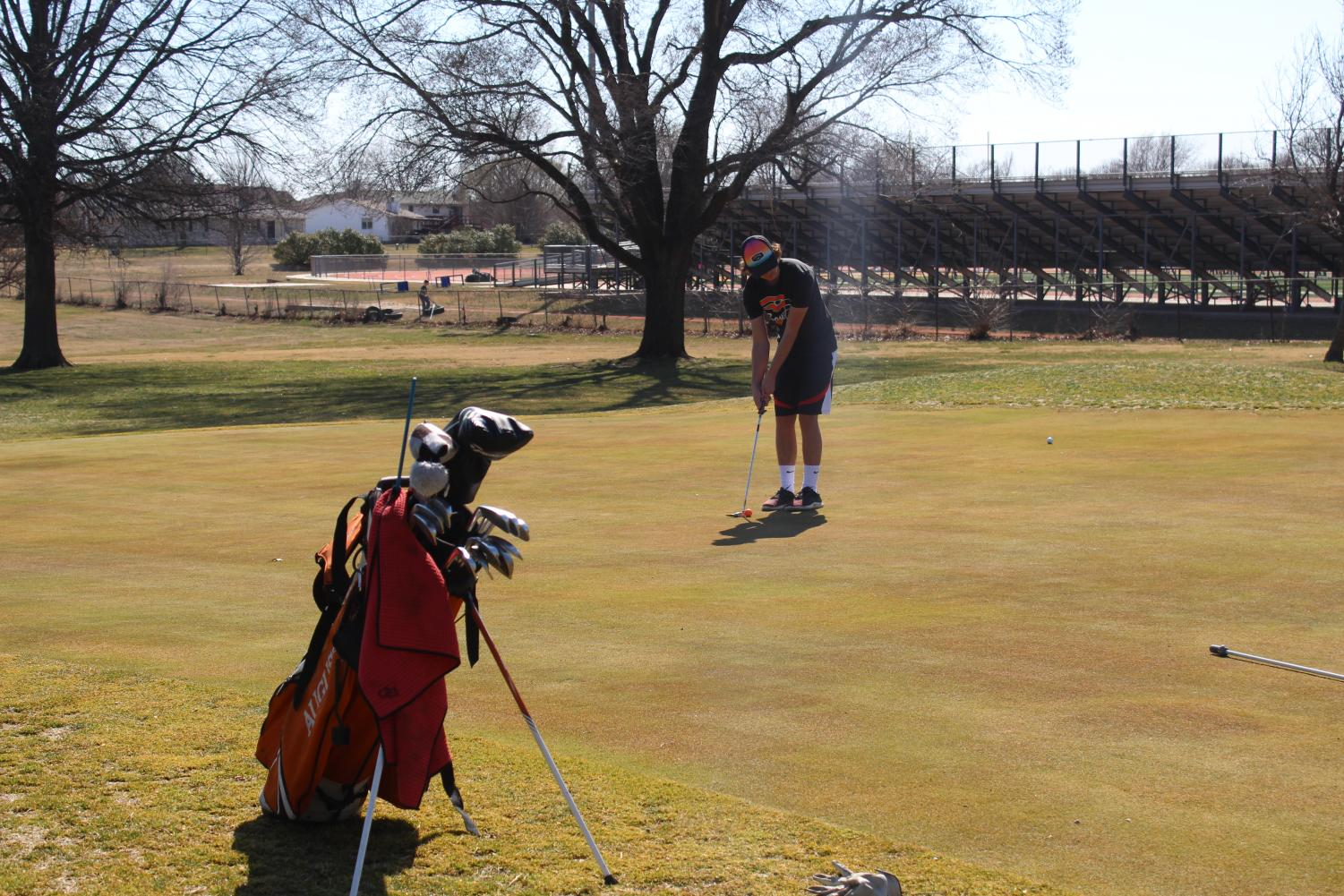 Kyle Scott (11) lines up his shot while practicing at the Augusta Country Club. This is where the JV Invitational was held.
