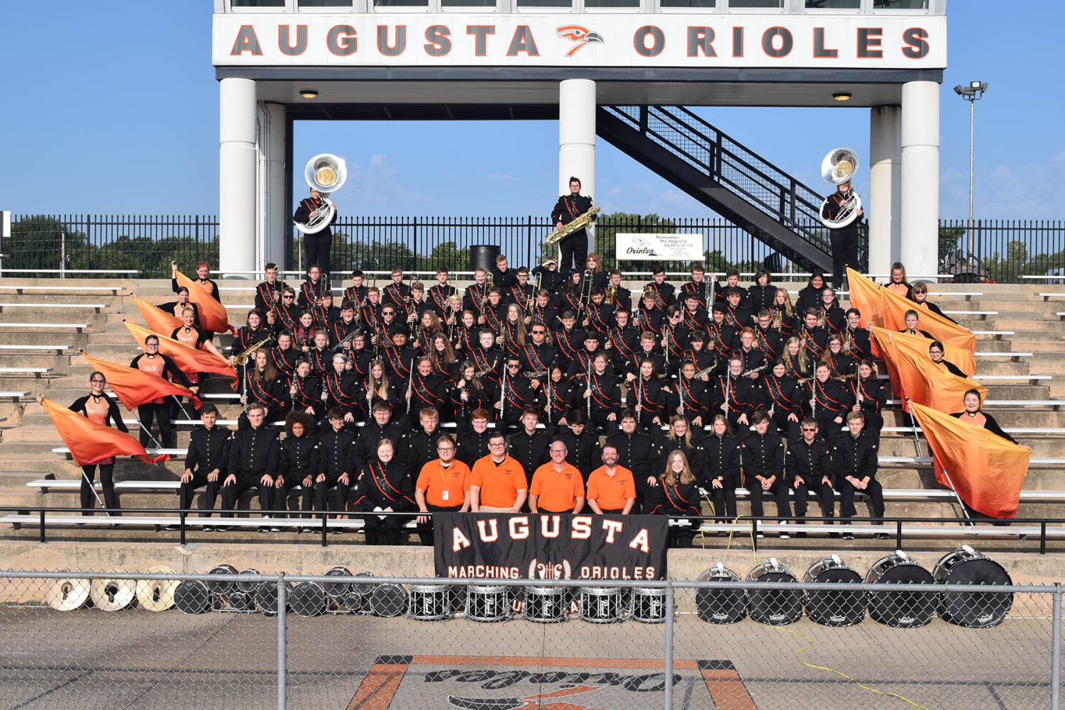 The band and color guard smiles for the annual marching band picture. The band rushed to get ready after their early morning practice.