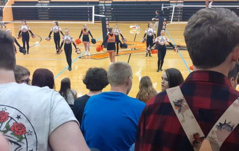 The cheerleading squad and the dance team try to raise the students' excitement for the upcoming sports season during the first day pep assembly Aug. 15 in Hutter Gym. All students contribute to the image of the school.