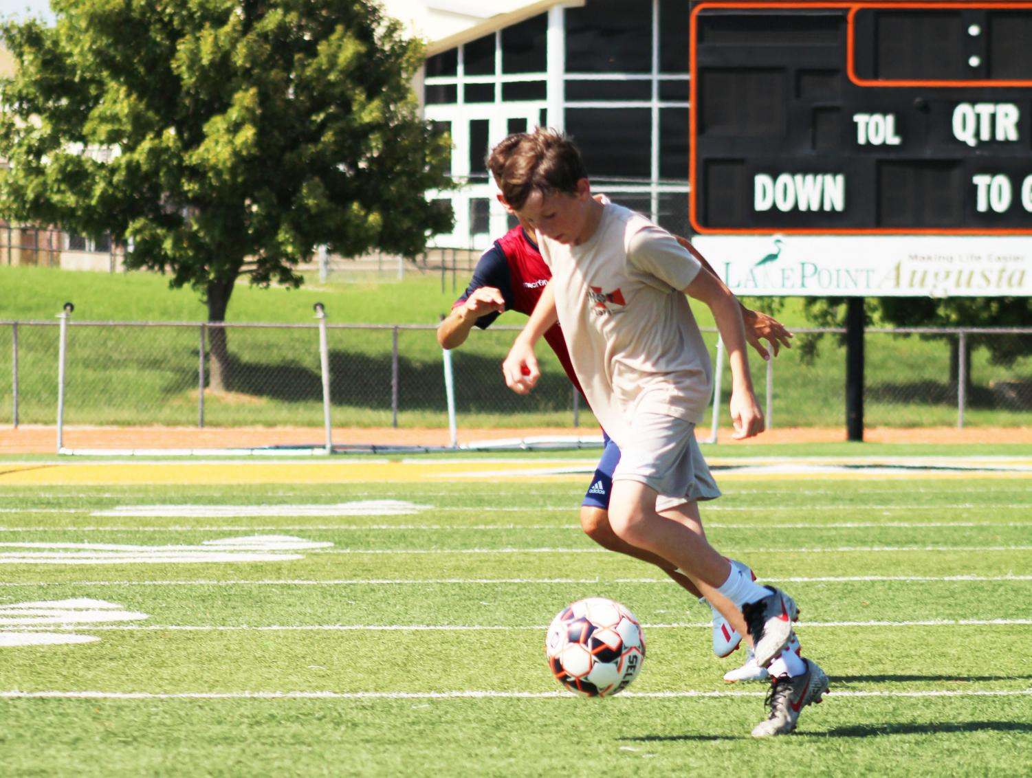 Freshman Kalvin LaPlant dribbles through the defender on the first day of fall sports tryouts. The boys soccer team practiced on the Hiller Stadium field after school.