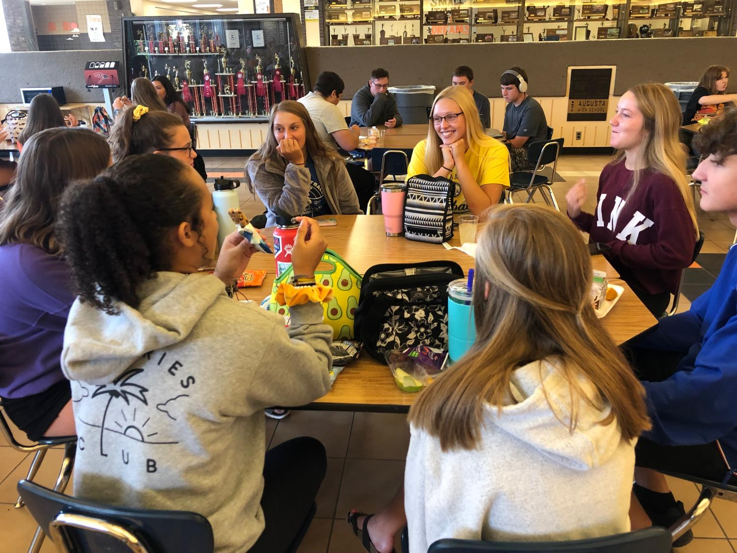 A group of students both eating and socializing at the same time. These students were laughing at a joke junior Ashlyn Bowen made.
