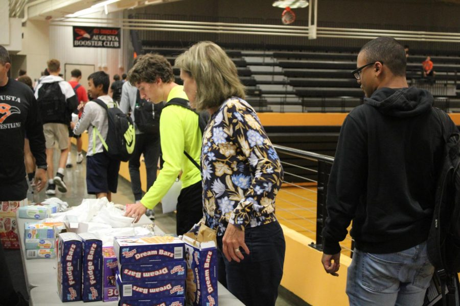 Principal Donna Zerr is over looking the ice cream table as students walk by getting their ice cream in Hutter Gym on October 9th.
