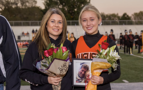 Senior Lexi Chinn and her mom Sherri Combs celebrate senior night Oct. 18. Chinn carried a photo of her dad who passed earlier this year.