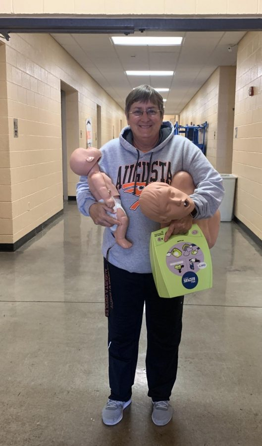 Health teacher Cynthia Phillips holds two CPR dummies and a practice AED kit. The school has been teaching students how to perform CPR for at least 10 years in health classes.