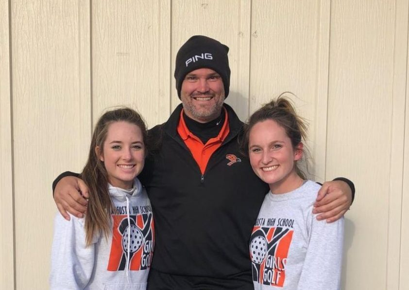 Freshman Alexa Zweifel, girls golf coach Danny Lundberg and senior Sarah Price posing in front of a building at the 4A State Golf Tournament.