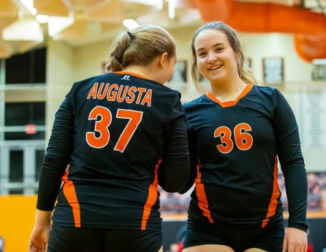 Freshman Alli Eastridge motivates her teammate Jenna Speere at their volleyball game. The team worked together to get the victory.