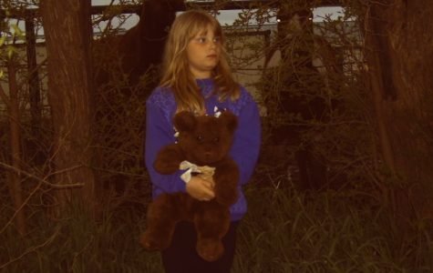 Raven Holland, around age six, holds a stuffed bear. Holland spent eight years in the foster care system before being adopted by her great aunt.