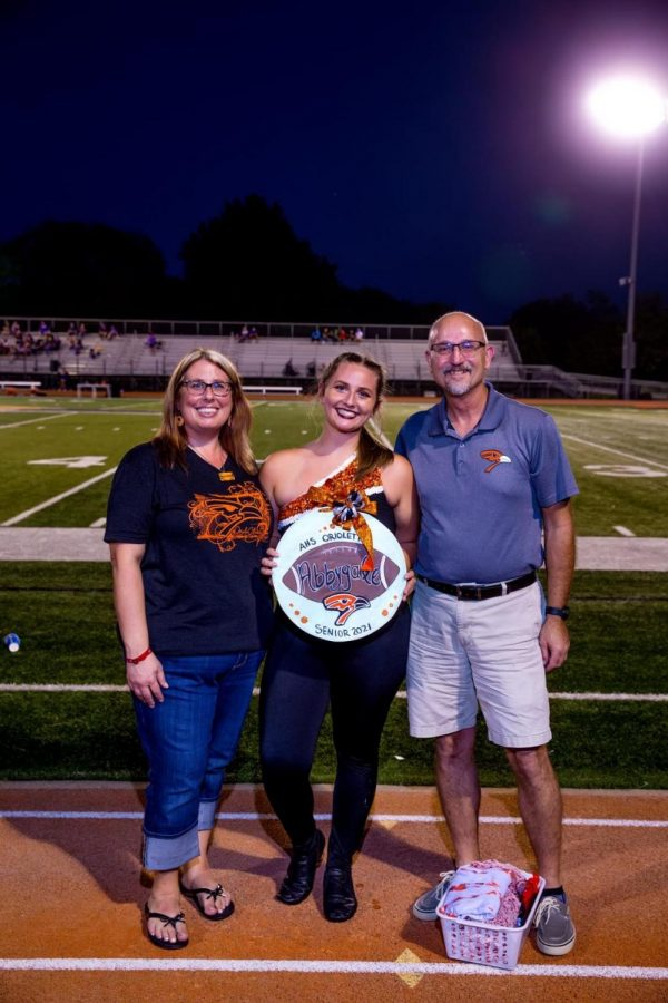 Senior Abbygale Laing stands with her parents after being recognized for the dance team. Laing's biggest accomplishment is that remembering the dances has gotten much better than when she first started dancing.