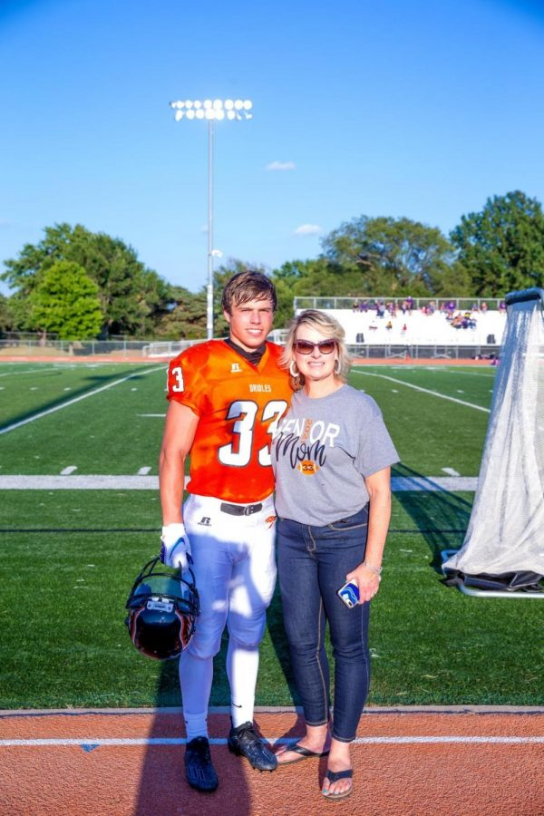 Senior Duke Lichlyter stands with his mom after being announced at senior night. Lichlyter's biggest accomplishment from his high school football career is that he was able to play with his best friends the past four years and watch them succeed in winning the first playoffs game since 2006.