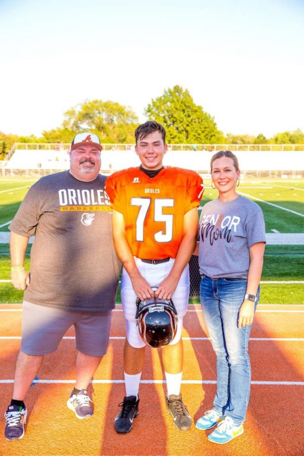 Senior Zack Timberlake stands with his parents during the senior recognition. Timberlake's biggest accomplishment in his high school career would be when they received second-team All-League in football.