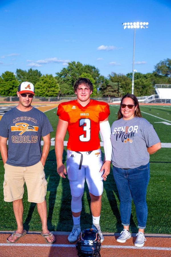 Senior Ryan Andrews stands with his parents for a picture after he is recognized at senior night. Andrews' biggest accomplishment from his high school football career is winning the playoff game for the first time under football coach Jason Filbeck.