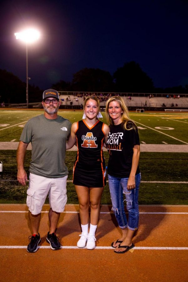 Senior Taylor Braungardt stands with her parents after being recognized for cheerleading at senior night. Braungardt's biggest accomplishment from her high school career is placing second at the state championship.