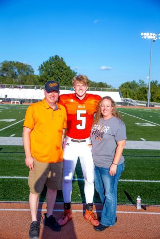 Senior Ely Wilcox stands with his parents on the track at Hillier Stadium after his name was announced. Senior night for football, cheerleading, dance, cross country, and golf was Friday, Sept. 4.