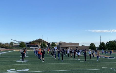 """The band practices  for their homecoming halftime routine playing """"Spirit in the Sky"""" by Norman Greenbaum and """"Escape"""" by Rubert Holmes. Co-band director Todd Hollis and drum major Madeline Natvig led the band in their warm ups."""