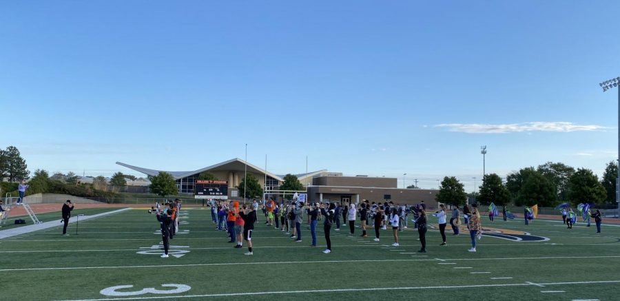 "The band practices  for their homecoming halftime routine playing ""Spirit in the Sky"" by Norman Greenbaum and ""Escape"" by Rubert Holmes. Co-band director Todd Hollis and drum major Madeline Natvig led the band in their warm ups."