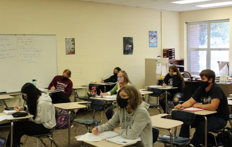 Students go over notes while wearing masks and social distancing in their third block math class. Students and teachers are supposed to social distance whenever possible.