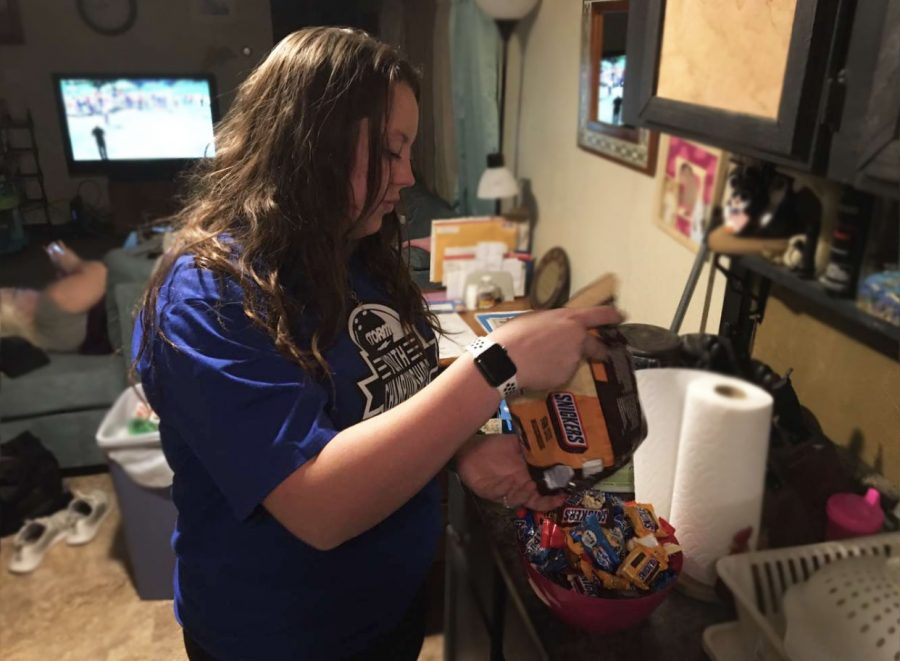 Junior Kassidy Miller prepares for Halloween by placing the candy in a bowl for trick or treaters. Miller plans on having hand sanitizer available after every child has grabbed a piece of candy.
