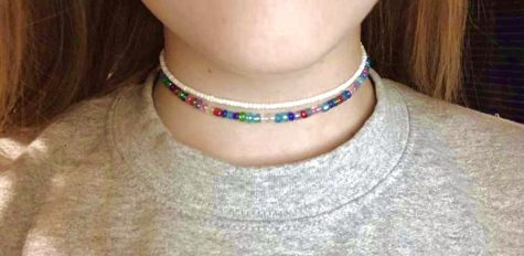 Junior Maddie Smart models two chokers that she made. To order jewelry from Smart visit her Instagram @maddies.mix; bracelets are $2, anklets are $3, chokers are $4, and necklaces are $5.