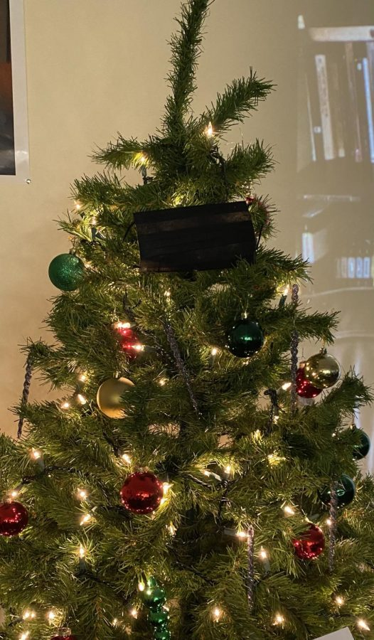 History teacher Brad Raine's Christmas tree sits at the front of his room with a mask on. Wearing a mask during the holidays could help protect individuals during celebrations according to the CDC.