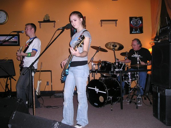Science teacher Joe Connor plays drums with his Leave Thursday bandmates Dave Kerwood and his sister Bre Kerwood. They played multiple Christian rock songs for the group in front of them.