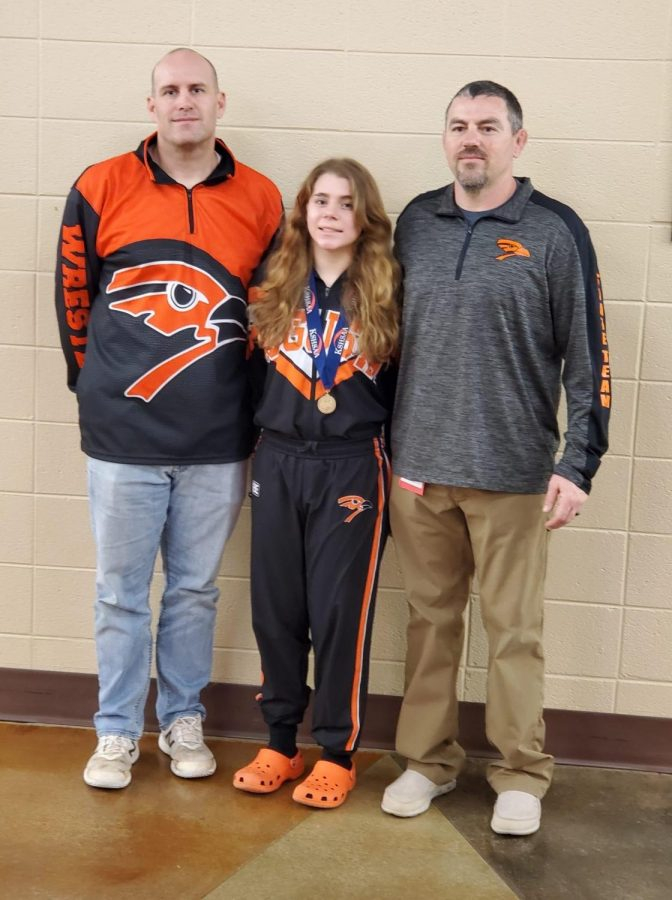 Freshman Jill High stands with head wrestling coach Brandon Terry and assistant coach Rhett Mallon after receiving her 5th place medal. All athletes that placed at the girls state Salina tournament on Feb. 26th received one.