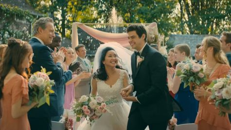 Lara Jean and Peter Kavinsky happily walk down the aisle on their wedding day. Lara Jean dreamt of the day the two got married after going to college together, but it never actually happened in the movie.