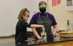 During the advanced chemistry magic show, senior Macie Goodmanson shows an elementary student a science experiment. Even during the chemistry show, students still had to wear masks, and some students and teachers hope that the mask mandate will hopefully be gone next year. Photo by Paige Harrington
