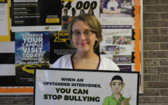 Sophomore Emma Neuschafer showcases the bullying poster found in the counselors office. This supports the bullying awareness cause that the student body in AHS has currently been taught since the first early stages of education.