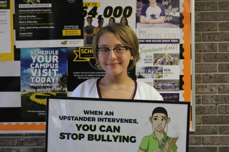 Sophomore+Emma+Neuschafer+showcases+the+bullying+poster+found+in+the+counselors+office.+This+supports+the+bullying+awareness+cause+that+the+student+body+in+AHS+has+currently+been+taught+since+the+first+early+stages+of+education.