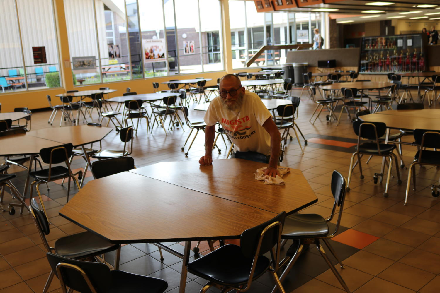 Head Custodian Steve Holladay wipes down tables after lunch for the next lunch period. Holladay has been replacing and restoring items that were stolen or damaged.