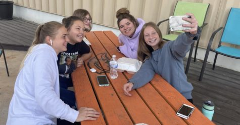 While eating outside for lunch, seniors Chloe Wells, Kirsten Woodard, Grace Logan, Haley Smith and Jamie Linder take a selfie. Students use photos as a way to capture their high school experience.