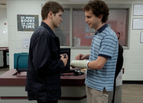 """After Connor (Colton Ryan) yelled at Evan (Ben Platt) in the hallway, they cross paths again in the library. Connor apologizes to Evan and signs his cast to make Evan feel good and says """"Now we can pretend we both have friends."""" ©Universal Pictures"""